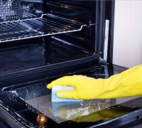 Close up of female hand with yellow protective gloves cleaning oven door